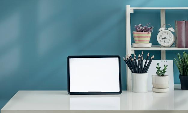 Mockup tablet schermo vuoto e decorare oggetto su tavolo bianco e parete azzurra.