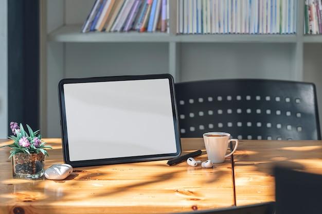 Mockup tablet schermo vuoto e gadget sul tavolo di legno in soggiorno con la luce del sole del mattino.