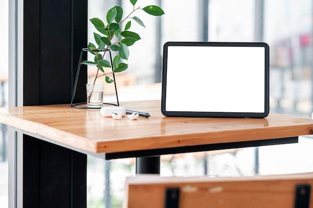 Tablet schermo vuoto mockup e gadget sulla tavola di legno.