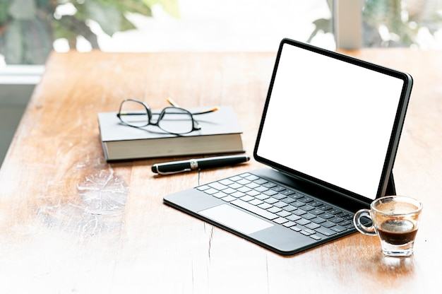 Tavoletta e tastiera mockup con schermo vuoto con percorso di ritaglio su tavolo di legno, schermo bianco vuoto per esposizione o montaggio di prodotti giovani.