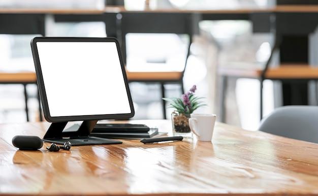 Tablet mockup schermo vuoto su supporto e gadget su tavolo di legno in co-workspace.