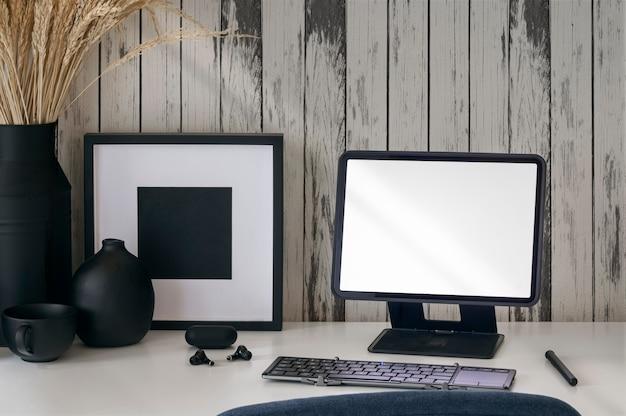 Tablet schermo vuoto mockup su supporto con tastiera e oggetto decorativo su tavolo di legno.