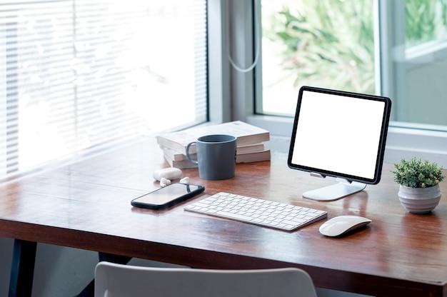 Tablet schermo vuoto mockup su supporto con tastiera e gadget su tavolo di legno in una moderna stanza dell'ufficio.