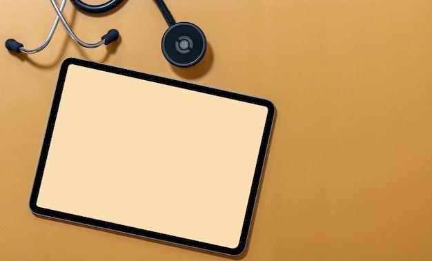 Mockup tablet schermo vuoto e stetoscopio su colore giallo