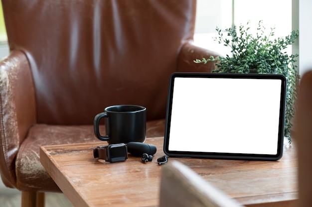 Tablet schermo vuoto mockup con gadget sulla vecchia tavola di legno nella caffetteria.