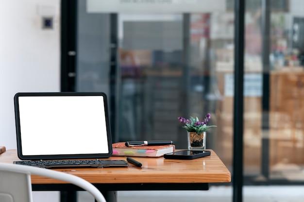 Tablet schermo vuoto mockup con tastiera e gadget sul tavolo di legno nella sala bar.