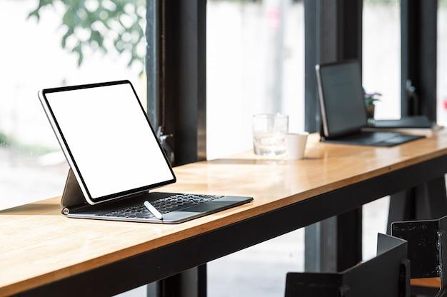 Tablet schermo vuoto mockup con tastiera su tavolo da banco in legno in co-workspace.