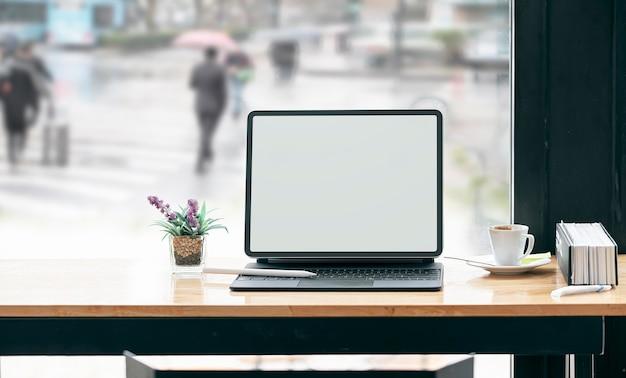 Mockup tablet schermo vuoto con tastiera sulla tavola di legno nella caffetteria.