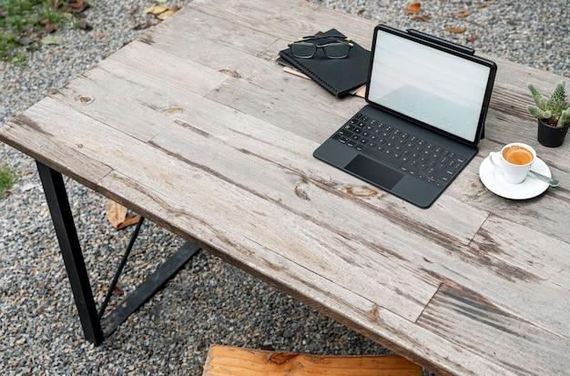 Tablet schermo vuoto mockup con tastiera magica, tazza di caffè e taccuino sul tavolo di legno all'aperto.