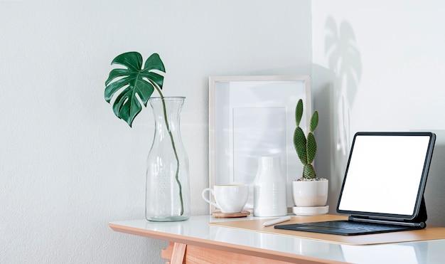 Tablet schermo vuoto mockup con tastiera magica e oggetti di documentazione su tavolo di legno in camera moderna.