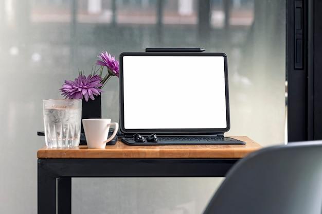 Tablet schermo vuoto mockup con tastiera magica su tabler in legno nella moderna stanza dell'ufficio.