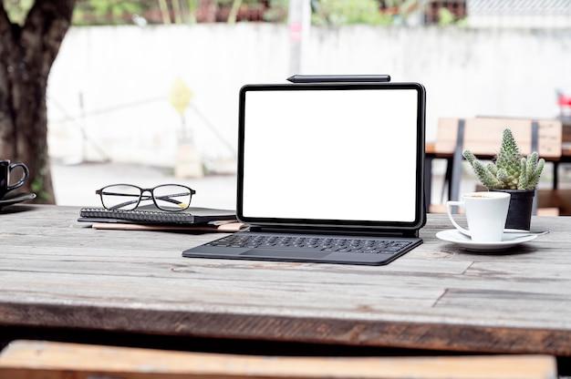 Tablet schermo vuoto mockup con tastiera magica su talbe in legno all'aperto.