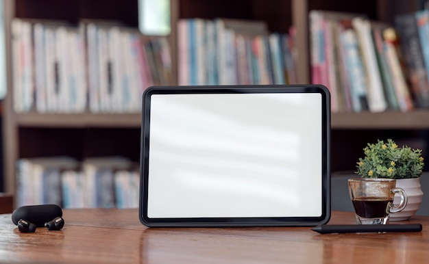 Tablet schermo vuoto mockup sul tavolo di legno con sfondo scaffale sfocato.