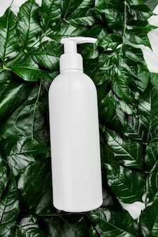 Mockup di bottiglia bianca vuota su foglie tropicali verdi, packaging cosmetico, vista dall'alto del tubo crema, composizione piatta