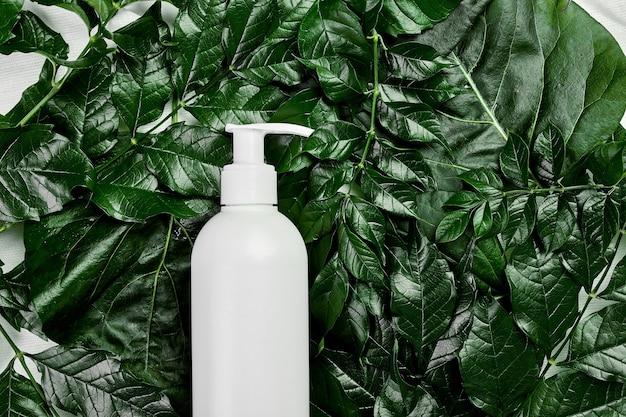 Mockup di bottiglia bianca vuota su foglie tropicali verdi, concetto di spa, plastica di imballaggio cosmetico biologico naturale, vista dall'alto del tubo crema, pubblicità di composizione piatta o modello di banner