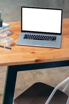 Computer portatile dello schermo bianco in bianco del modello nella vista verticale sulla tavola di legno.