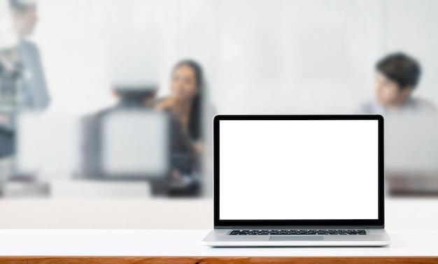 Computer portatile dello schermo bianco in bianco del modello sulla tavola superiore bianca con fondo della sfuocatura della gente di affari.