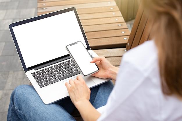 Mockup schermo bianco vuoto laptop e smartphone sfondo spazio vuoto per pubblicizzare la digitazione del testo