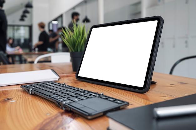 Tablet e tastiera portatili con schermo bianco vuoto mockup in co-workspace.