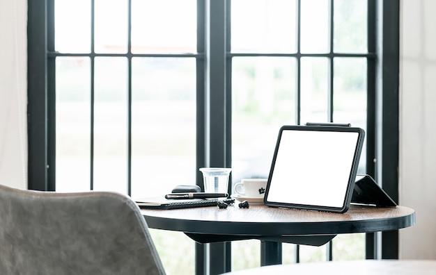 Mockup tablet schermo bianco vuoto e gadget sulla tavola rotonda in legno nella sala bar.