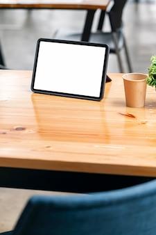 Tablet schermo bianco vuoto mockup sul tavolo di legno nella sala bar, vista verticale.