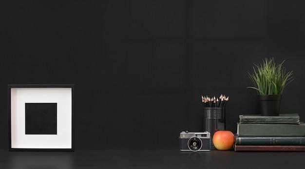 Mockup in bianco cornice in legno e oggetti di decorazione su sfondo nero.