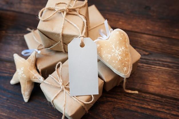 Scatole mockup per regali di carta kraft e etichette regalo su uno sfondo di legno
