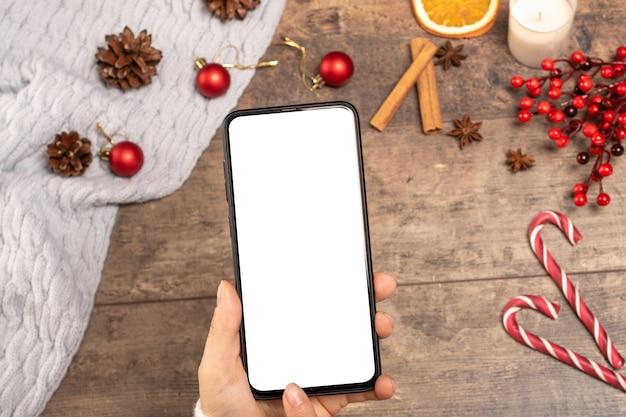 Mockup cellulare sulla tavola di legno di sfondo durante le vacanze di natale.