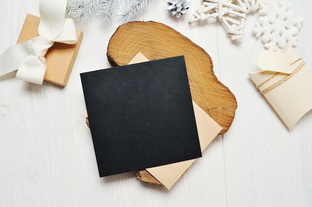 Lettera di cartolina d'auguri di natale nero mockup in busta e regalo con albero bianco, flatlay su un fondo di legno bianco.