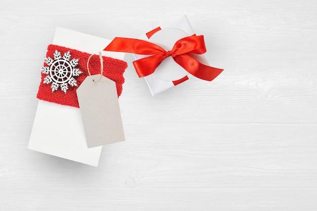 Confezione regalo di natale mockup e tag su sfondo di legno con fiocchi di neve, biglietto di auguri buon natale