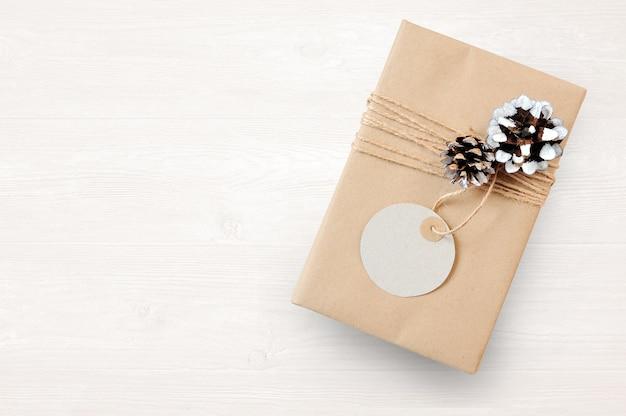 Mockup confezione regalo di natale avvolta in carta riciclata marrone e corda per sacco legata e taggata con, vista dall'alto
