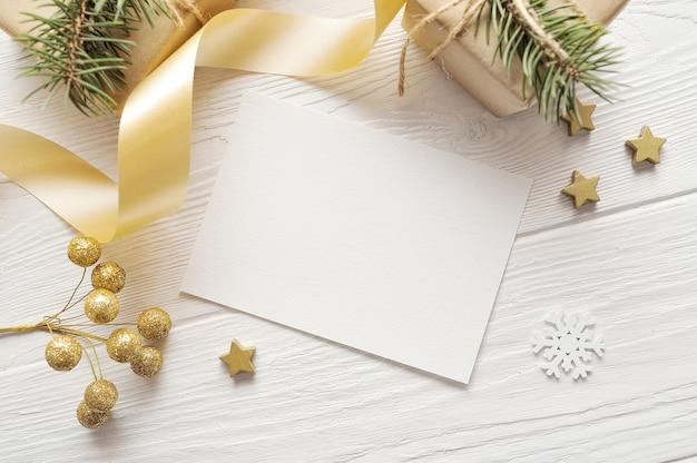 Mockup biglietto di auguri di natale vista dall'alto e stella d'oro, flatlay su uno sfondo di legno bianco con un nastro.