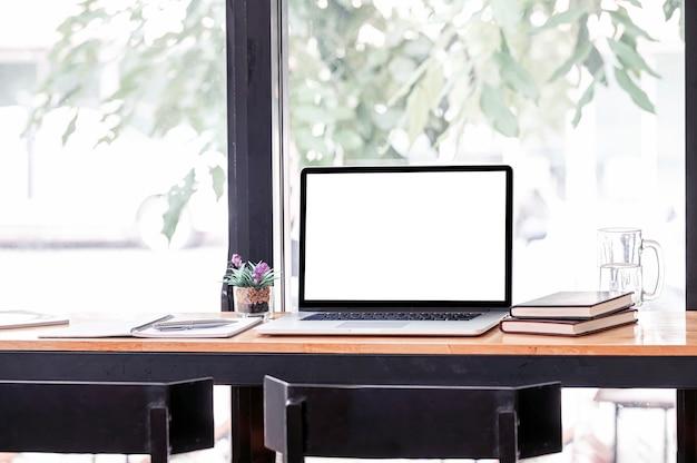 Area di lavoro creativa mockup con computer portatile a schermo vuoto su tavolo da banco in legno.