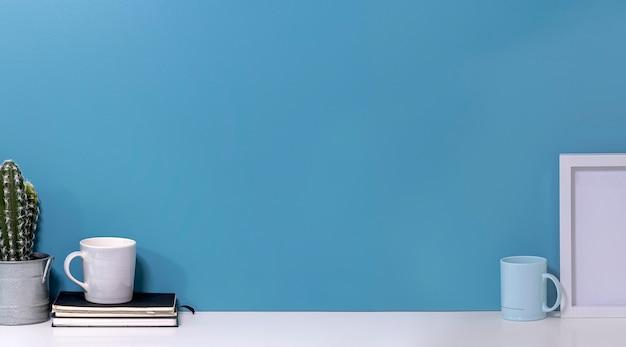 Mockup di spazio di lavoro creativo con tazza, cactus, libro e cornice in legno