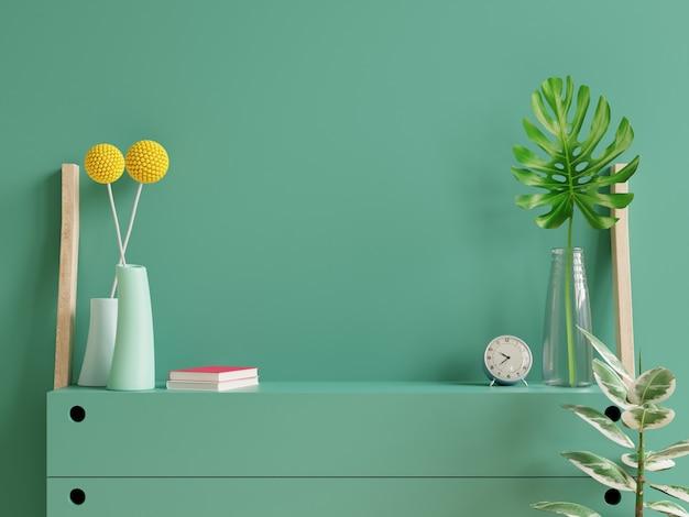 Mockup parete verde scuro con piante ornamentali e elemento decorativo su cabinet.3d rendering