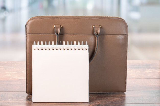 Mockup di blocco note vuoto e valigetta aziendale in piedi sul tavolo. su uno sfondo sfocato di ufficio. pianificare una giornata lavorativa in ufficio
