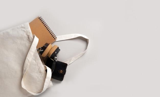 Mockup modello vuoto shopping bag crema bianca per il tuo design, eco friendly, zero sprechi con spazio copia. minimalismo piatto. all'interno ci sono delle cuffie, un taccuino e un portafoglio da uomo.