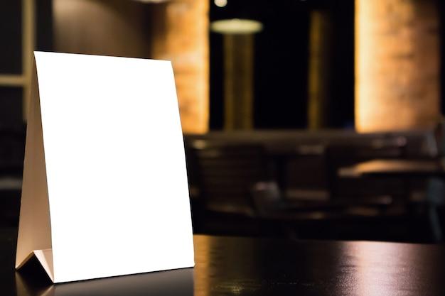 Mockup cornice del menu etichetta bianca vuota sul tavolo con sfondo interni ristorante caffetteria