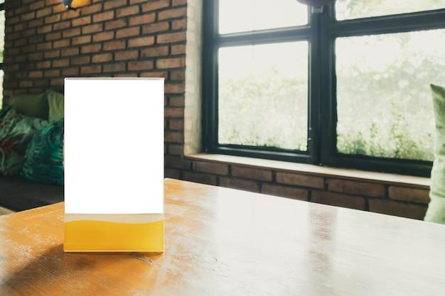 Mockup cornice del menu etichetta bianca vuota sul tavolo con finestra ristorante caffetteria