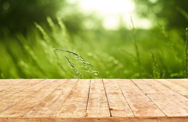 Modello. svuoti la tavola di legno della piattaforma con il fondo del bokeh del fogliame.