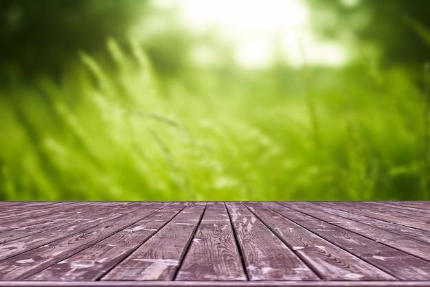 Modello. svuoti la tavola di legno della piattaforma con lo spazio del bokeh del fogliame.