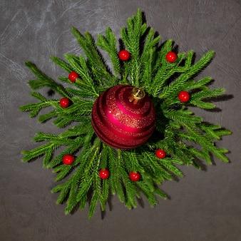 Mockup di rami verdi con una palla di natale rossa capodanno e natale vista dall'alto