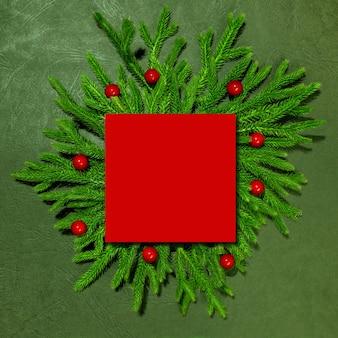 Un mockup di rami verdi con una carta di carta rossa per l'iscrizione capodanno e natale vista dall'alto