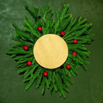 Un modello di rami verdi con una carta di carta rossa per l'iscrizione capodanno e natale