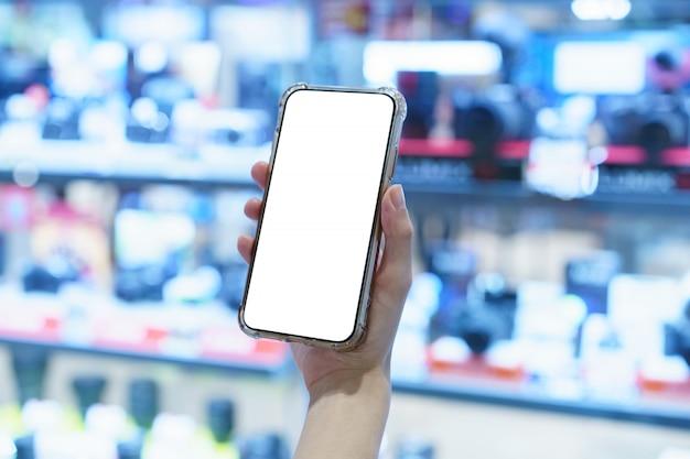 Mockup, mani che tengono il telefono cellulare con schermo bianco vuoto nel negozio di visualizzazione della fotocamera offuscata