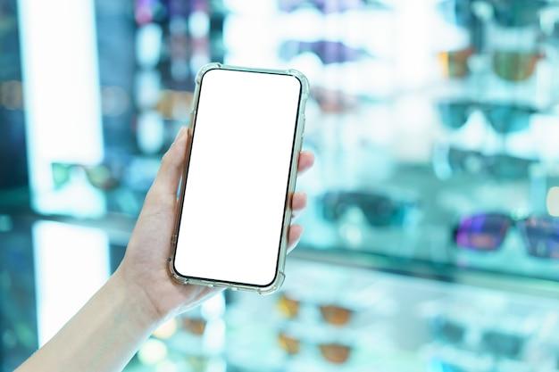 Mockup, mani che tengono il telefono cellulare con schermo bianco vuoto nel negozio di occhiali sfocati, concetto di pagamento digitale