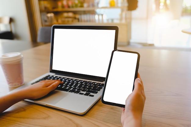 Computer immagine mockup, schermo vuoto del telefono cellulare per la digitazione del testo a mano, utilizzo del computer portatile contatto aziendale alla ricerca di informazioni sul posto di lavoro sulla scrivania in ufficio.