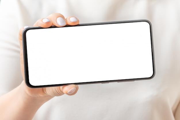 Immagine del modello della mano femminile che tiene e che mostra telefono cellulare nero con lo schermo in bianco. avvicinamento