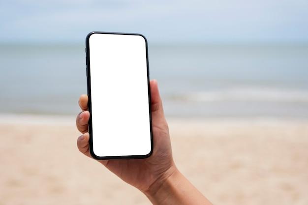 Immagine mockup di una mano che tiene un telefono cellulare nero con schermo desktop vuoto in riva al mare