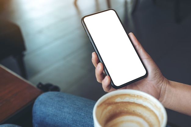 Immagine di mockup di una mano che tiene il telefono cellulare nero con schermo vuoto mentre si beve il caffè nella caffetteria